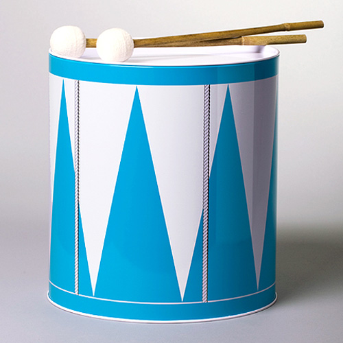 A tin can drum in three different colours with a pair of bamboo drumsticks