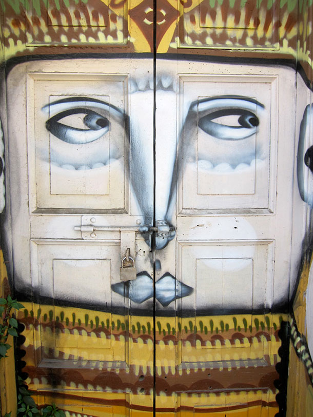 A painted face at a door