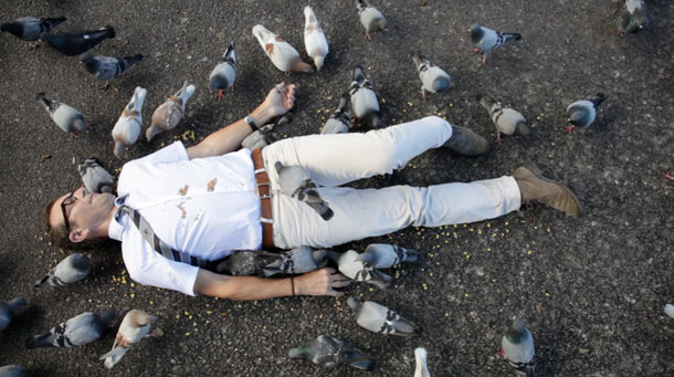 A man on the ground with pigeons all over him